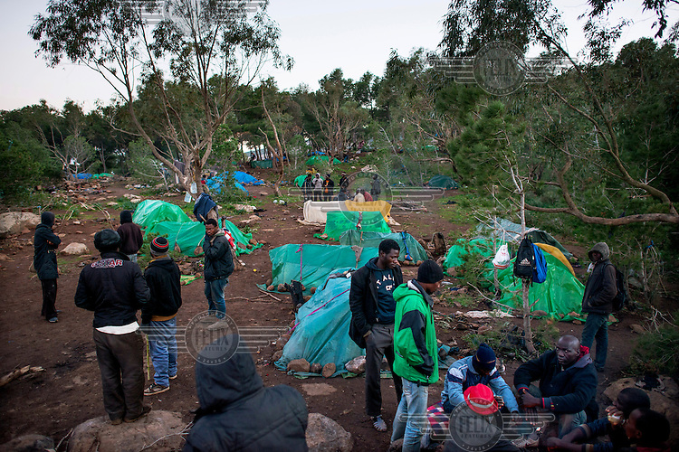 A group of migrants from Sub-Saharan Africa at their camp in the Gurugu Mountains. About 1200 migrants have set up a camp there deep in a forest, hidden from the police and authorities. It is is near the Spanish exclave of Melilla and many of the migrants try to break into the city in hope of eventually finding a way to enter Europe.