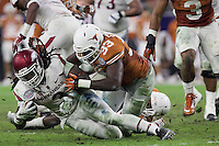 Arkansas Democrat-Gazette/BENJAMIN KRAIN --12/29/14--<br /> BAlex Collins is tackled by Texas defender Steve Edmond in the 4th quarter of the Razorbacks victory over Texas in the Texas Bowl.