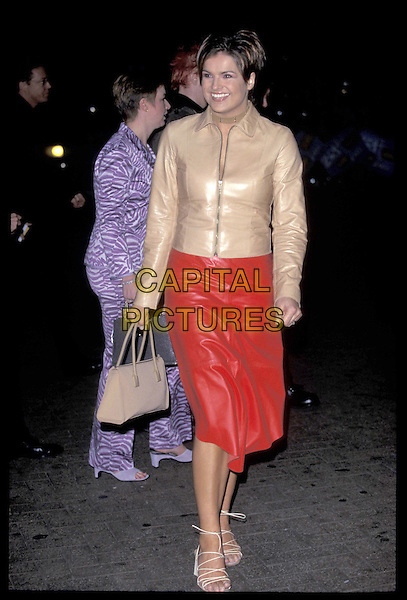 KATY HILL.London,.03 March 2000..full length full-length red leather skirt beige jacket smiling white teeth.ref:9403.www.capitalpictures.com.sales@capitalpictures.com.©Capital Pictures