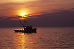 Fishing boat with silhouetted boat and men fishing sunset Puget Sound off Edmonds Washington State USA.