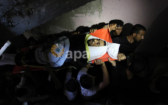 Mourners carry the body of Palestinian Yousef Abu Kamil, who was died hit by an Israeli airstrike during his funeral in Gaza city on November 14, 2019. Photo by Mahmoud Ajjour