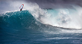 USA, Hawaii, Maui, a man windsurfs and gets air on a huge wave at a break called Jaws or Peahi
