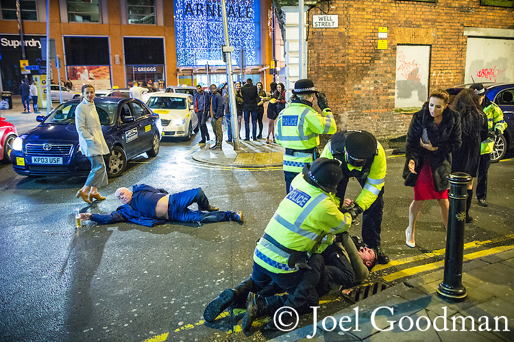 © Joel Goodman - 07973 332324 . NO SYNDICATION , ONWARD SALE OR TRANSFER PERMITTED . 01/01/2016 . Manchester , UK . Police detain a man whilst another lies collapsed in the road . Revellers in Manchester on a New Year night out at the clubs around the city centre's Printworks venue . Photo credit : Joel Goodman