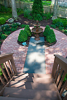 Small circular patio shade garden with patterned brick, blue flagstone, evergreens, hostas, shrubs, trees, picket fence, looking from top of stairs, lawn grass, fountain focal point