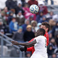 University of Connecticut forward Mamadou Diouf (23) and University of New Mexico defender Travis Campbell (6) battle for head ball. .NCAA Tournament. With a goal in the second overtime, University of Connecticut (white) defeated University of New Mexico (red), 2-1, at Morrone Stadium at University of Connecticut on November 25, 2012.