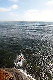 USA, California, San Diego, surfer heads down the stairs and into the water at Ocean Beach