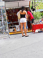 A young woman with very small tight shorts hotpants looking at a stall selling tourist souvenirs and sun glasses. The source of the Buna river and the house of the Whirling Dervishes, an old Muslim monastery, Blagaj. Federation Bosne i Hercegovine. Bosnia Herzegovina, Europe.