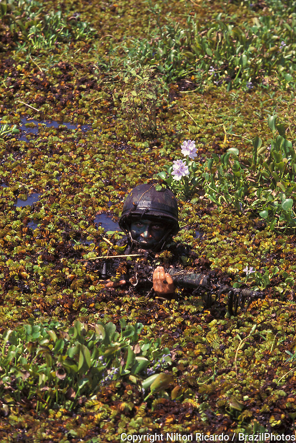 Brazilian Army soldier during training in jungle. Camouflage in swamp, body painting.