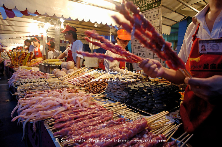 Market vendors selling seafood on skewers at Wangfujing night market, Beijing, China.