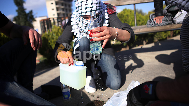 A female Palestinian protester prepares a molotov cocktail during clashes with Israeli security forces in Beit El on the outskirts of the West Bank city of Ramallah, November 29, 2015. Photo by Shadi Hatem