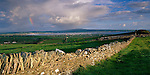 County Clare, Ireland<br /> Rainbow and clearing storm, stone fence and pastures near Lahinch on Liscannor Bay