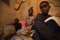Abebe, HIV positive, and in crritical conditions, lies on his house bed while his son and his wife look after him in Addis Ababa, Ethiopia on Tuesday June 06 2006.