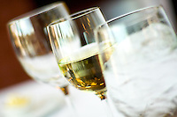 A Glass half filled with white wine in between a glass of ice and a glass of water