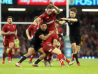 Pictured: Leigh Halfpenny of Wales (with ball) assisted by Cuthbert of Wales (TOP), is tackled by Charles Piutau of New Zealand, Alex  HSaturday 22 November 2014<br />