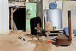 A Palestinian woman fills plastic bottles and jerry cans with drinking water from a water tank in the West Bank village of Um Alkhair south of Hebron on August 17, 2016. Photo by Wisam Hashlamoun