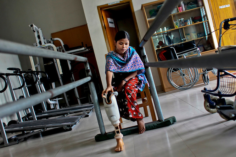 Bangladeshi garment worker Aroti, 16, who worked on the 5th floor of Rana Plaza, sits with her artificial leg at a hospital in Savar, near Dhaka, Bangladesh, Sunday, June 23, 2013.