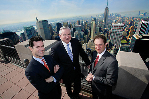 A group photo of real estate executives on a rooftop overlooking midtown Manhattan.