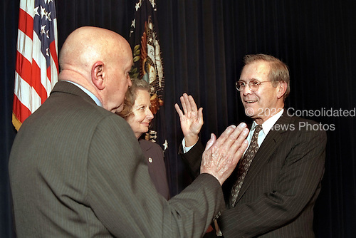 Donald H. Rumsfeld (right) is administered the oath of office as the 21st Secretary of Defense by David O. Cooke (left), as Joyce Rumsfeld holds the Bible in a ceremony at the Eisenhower Executive Office Building on Jan. 20, 2001.  Rumsfeld was previously the 13th Secretary of Defense from 1975 to 1977.  Cooke is the director of Administration and Management at the Department of Defense. <br /> Mandatory Credit: Hyungwon Kang - White House via CNP