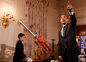 United States President Barack Obama points to the wall after fourteen year old Joey Hudy, from Phoenix, Arizona shot a marshmallow from the Extreme Marshmallow Cannon which he invented, while touring student science fair projects on exhibt in the State Dining Room at the White House in Washington, D.C. on February 7, 2012. Obama hosted the second White House Science Fair celebrating the student winners of science, technology, engineering and math (STEM) competitions from across the country. .Credit: Molly Riley / Pool via CNP