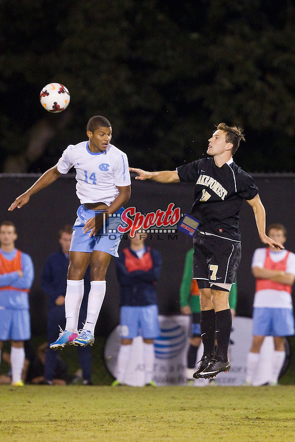 Omar Holness (14) of the North Carolina Tar Heels battles for a jump ball with Andy Lubahn (17) of the Wake Forest Demon Deacons at Spry Soccer Stadium on September 28, 2013 in Winston-Salem, North Carolina.  The Demon Deacons and the Tar Heels played to a 1-1 tie.  (Brian Westerholt/Sports On Film)