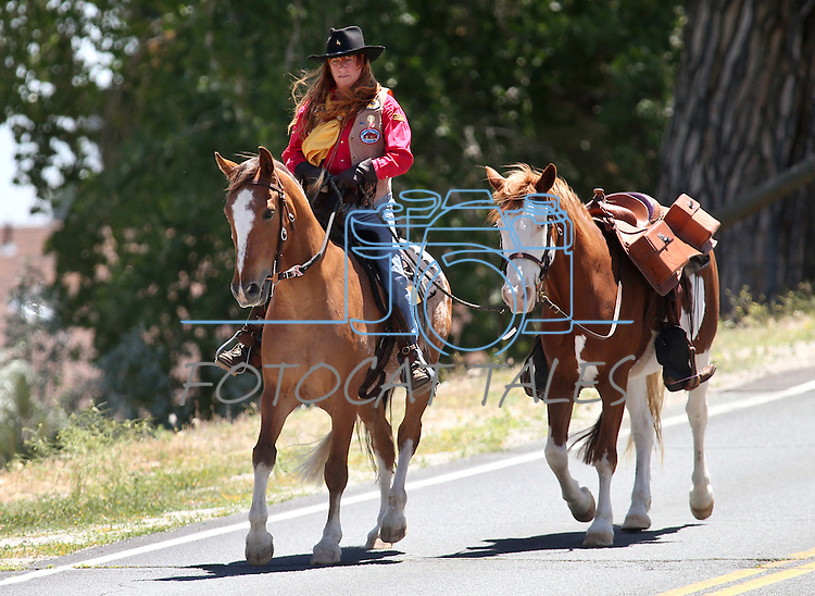 Deby O'Gorman, of Genoa, rides into downtown Carson City during the annual Pony Express Re-ride, on Thursday, June 12, 2014. O'Gorman led a riderless horse in honor of Sandy Blair, a board member who died since the last ride. (Las Vegas Review-Journal/Cathleen Allison)