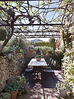 An intimate dining area on the original stone walled terrace with a marble topped table and shaded by a vine covered pergola