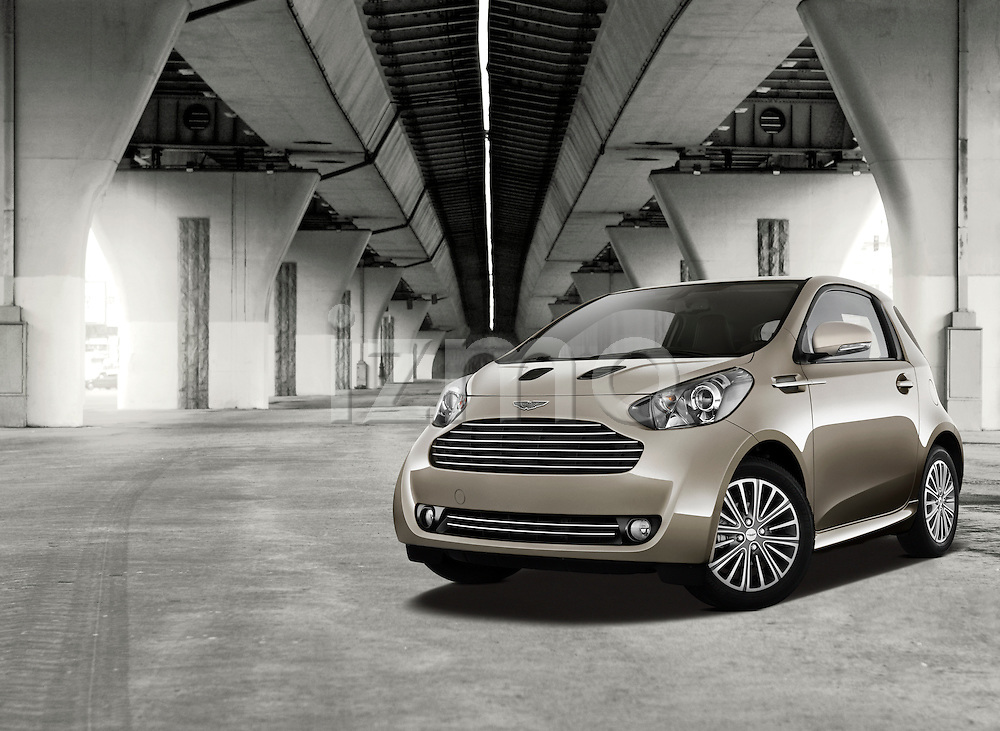One bronze 2011 Aston Martin Cygnet Micro Car outdoors under a overpass.