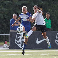 Portland Thorns FC forward Alex Morgan (13) challenges clearing attempt by Boston Breakers defender Julie King (8). In a National Women's Soccer League (NWSL) match, Portland Thorns FC (white/black) defeated Boston Breakers (blue), 2-1, at Dilboy Stadium on July 21, 2013.