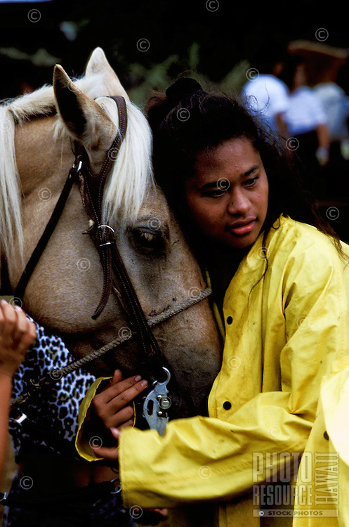 Girl wearing yellow raincoat holds the head of her horse at the Naalehu Rodeo on the Big Island of Hawaii.
