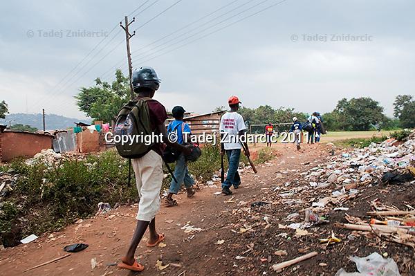 Augustus Owinyi, 12, (L), Felix Barugahare, 11, (middle), and Ivan Matovu, 13, walk to baseball practice at sports field of St. Peter's School in Nsambya, neighbourhood of Kampala, Uganda. Nsambya is a densily populated working-class neighbourhood in Kampala, not far from city center.