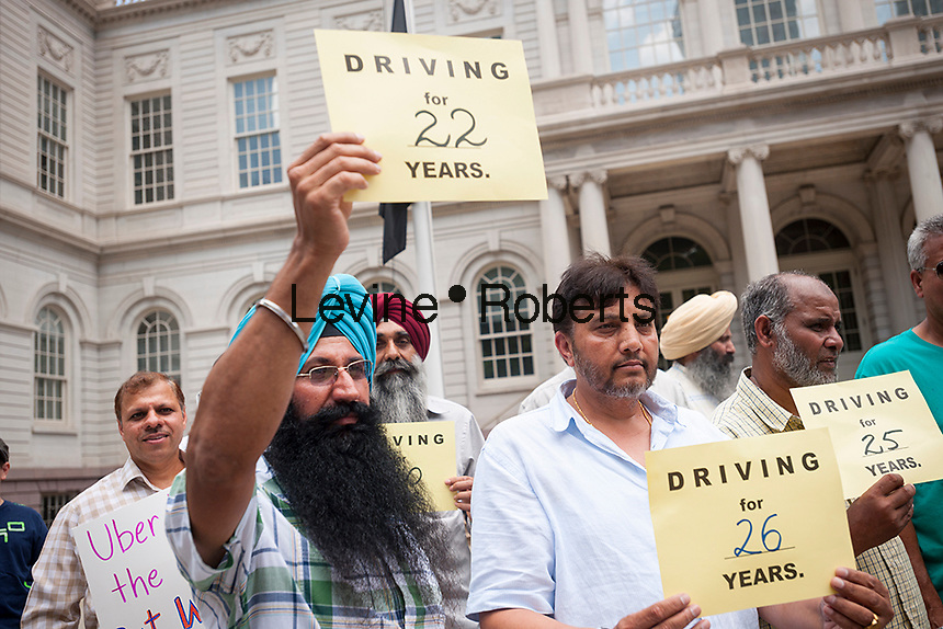 Taxi drivers and supporters rally on the steps of New York City Hall on Monday, July 20, 2015 for a cap on For-Hire-Vehicles (FHV) allowed on the city's streets, specifically e-hail services like Uber and Lyft. The New York City Council is scheduled to vote on the cap and both Uber and the Taxi Industry are lobbying the councilmembers. (© Richard B. Levine)