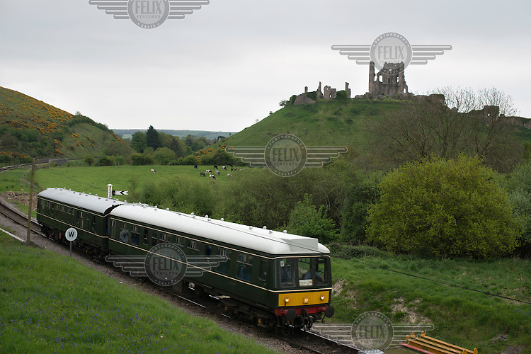 A diesel train from the Swanage Railway runs past Corfe Castle in Dorset.
