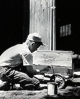 Boy painting name on his toy wagon. 1950's.
