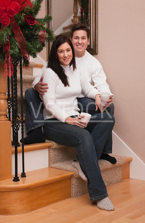 USA, Illinois, Metamora, mid adult couple sitting on steps and holding mugs