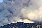 A helicopter carries a bucket of water towards the burning brush in the 2003 San Diego County fire.