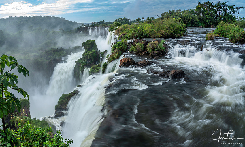 Iguazu Falls National Park in Argentina.  A UNESCO World Heritage Site.  Pictured is the precipice of Mbigua Falls and San Martin Falls with a stone arch or window in the background at the end of the falls.