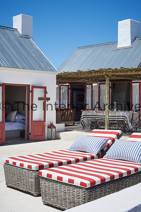 Two wicker sun loungers with red and white striped cushions on a terrace of a beach house.