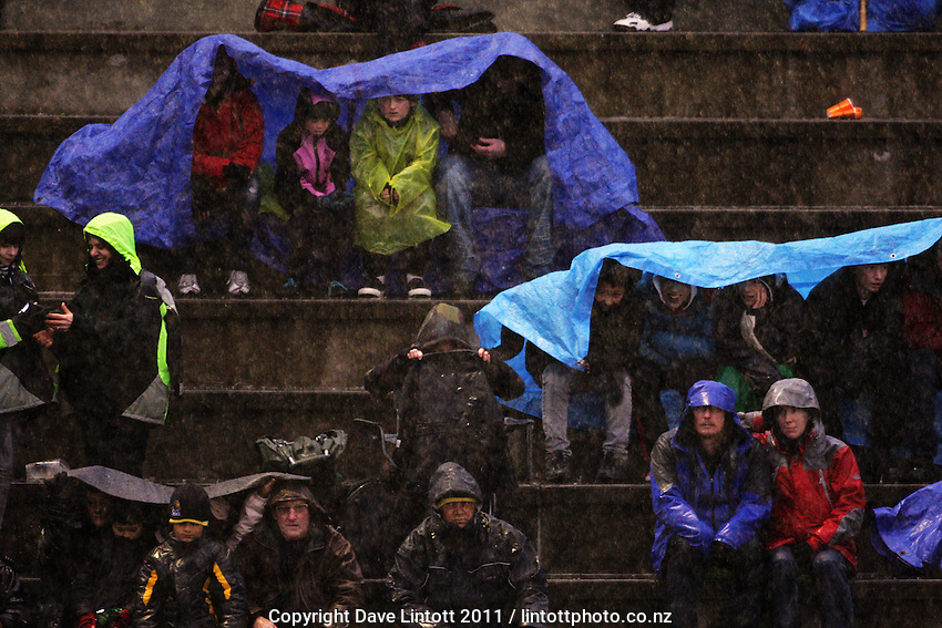 Fans watch the final in the hail and rain. Auckland Fury v Central Mavericks men's final of the Ford New Zealand National Hockey League 2011 tournament at National Hockey Stadium, Wellington, New Zealand on Sunday, 14 August 2011. Photo: Dave Lintott / lintottphoto.co.nz