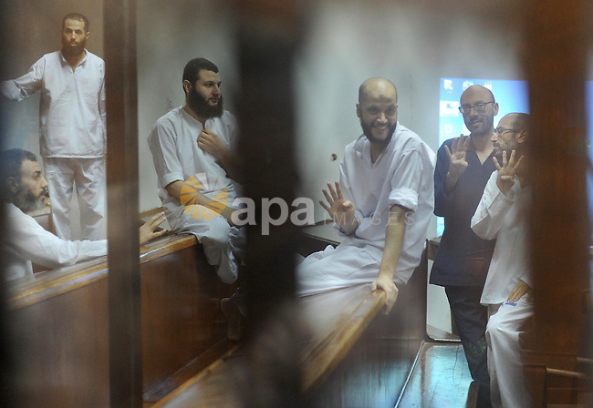 Egyptian Muslim Brotherhood Members gesture as they from the defendants cage as they attend their trial along with former president Mohamed Morsi at the police academy on the outskirts of the capital, on June 14, 2015. Cairo criminal court resumes Sunday the trial of deposed president Mohamed Morsi and 10 others on charges of espionage and leaking classified documents related to the national security and the army. Photo by Amr Sayed