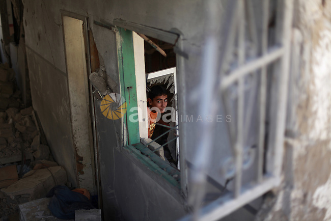 "A Palestinian boy searches in the debris of his family's house after it was hit by an Israeli military strike in Gaza city on August 10, 2014. A senior Hamas official said there was a ""weak"" possibility that Gaza truce talks would succeed and that Palestinian negotiators could leave Cairo after a meeting with Egyptian mediators. Photo by Ezz Zanoun"