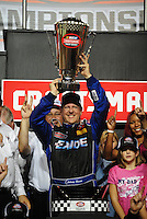 Nov. 14, 2008; Homestead, FL, USA; NASCAR Craftsman Truck Series driver Johnny Benson lifts the championship trophy after winning the 2008 championship following the Ford 200 at Homestead Miami Speedway. Mandatory Credit: Mark J. Rebilas-