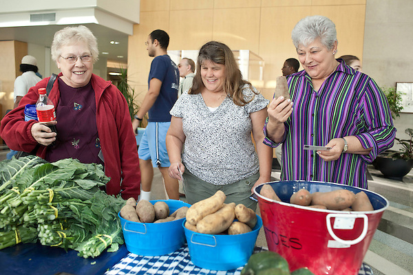 November 23, 2010. Chapel Hill, NC.. (left to right) Brenda Gooding, Cindi Letchworth and Rose Moseley, look over the 3 types of sweet potatoes sold by Stanley Hughes at the UNC Hospital Farmer's Market..   The sweet potato seems to be having a comeback, with many farmers increasing their planting of the potato's numerous varieties, as well as many restaurants including it on their menu in various forms such as the ever popular sweet potato fry.