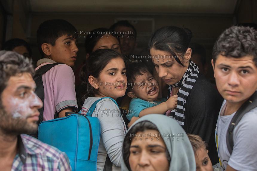 Folla di migranti all'interno di un vagone ferroviario, un bambino piange in braccio alla madre<br /> Crowd of migrants in a railcar , a baby is crying in his mother's arms