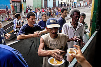 A Colombian missionary organization distributes food in the slum of Calvario, Cali, Colombia, 20 April 2004. Calvario, a slum right in the centre of the city, is considered the social bottom of Cali society. Poor dwellers recollect the garbage in the near city centre to sell it for recycling, while their children get high by sniffing the shoe glue on the dirty streets of ghetto. The order in Calvario is maintained by the illegal authorities, usually former policemen or army members, who set their own rules. Criminality, drug abuse, unemployment never allow the slum people jump off the misery and stop being the second category citizen within the rigid society of Colombia. Although Christian missionary organizations attempt to provide help, the overall situation does not improve.