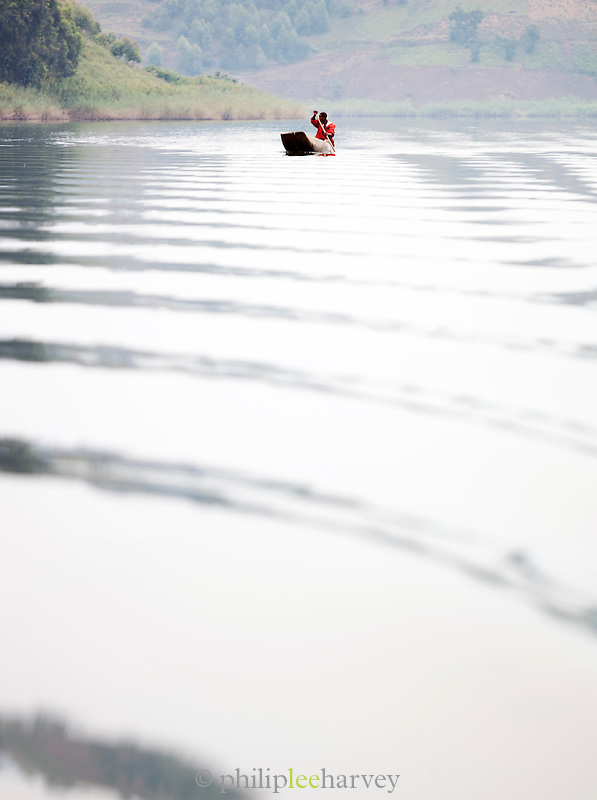 Man paddling in a small rowing boat on Lake Bunyonyi in South Western Uganda