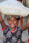 A young girl carrying goods on her head with a big smile