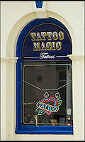 BNPS.co.uk (01202 558833)<br /> Pic: PeterWillows/BNPS<br /> <br /> ***Please use full byline***<br /> <br /> Staff at a quiet seaside tattoo studio were shocked when their latest customers walked in - Zayn Malik and his girlfriend Perrie Edwards.<br /> <br /> The One Director singer was visiting the harbour town of Weymouth in Dorset last week and made sure to add to his extensive tattoo collection while he was there.<br /> <br /> He asked for a Native American style design in black and grey ink with white highlights which featured the face of a wolf and two beaded feathers.<br /> <br /> The tattoo was etched onto his left calf and took around two hours to complete at a cost of 150 pounds.<br /> <br /> The 20-year-old pop icon was wearing long grey shorts with a button-down denim shirt and Dr Martens shoes, which he kicked off for his time in the tattooists chair.