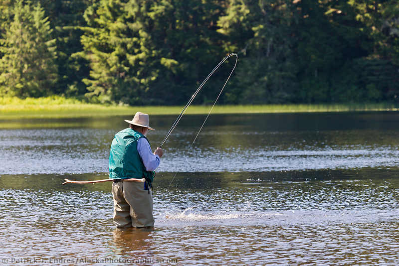 Fly fisherman with fish on the line, Ward Lake in Ketchikan, Alaska.
