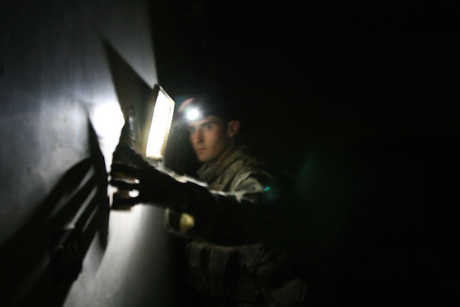 Spc. Daniel Lenihan, 23, of Rancho Lucamonga, Calif., a soldier with 1st Squadron, 40th Cavalry Regiment checks behind a picture frame while searching the house of a suspected al Qaida insurgent in the village of Abu Sayifi, Iraq, south of Baghdad. Sept. 19, 2007. DREW BROWN/STARS AND STRIPES