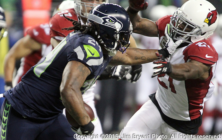 Seattle Seahawks  running back Marshawn Lynch (24) stiff arms Arizona Cardinals cornerback Patrick Peterson (21) at CenturyLink Field in Seattle, Washington on November 15, 2015. The Cardinals beat the Seahawks 39-32.   ©2015. Jim Bryant photo. All Rights Reserved.